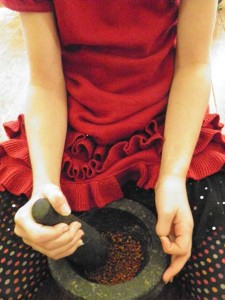 Grinding Sumac berries with a mortar and pestle