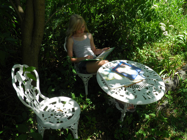 A young girl sits at a table outside under a tree reading some children's herb storybooks.