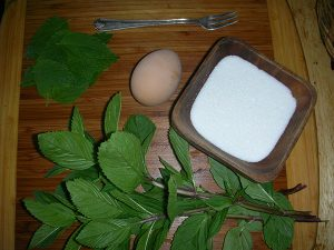 Fresh peppermint leaves, an egg, white sugar, and a fork on a wooden cutting board